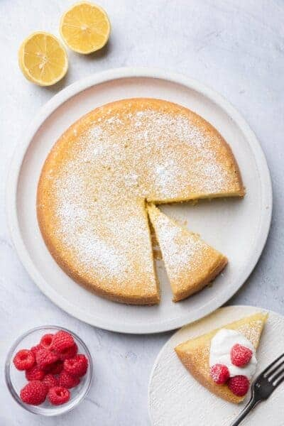 Large plate of olive oil cake with slice cut out on plate