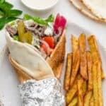 Beef shawarma wrap rolled up in a pita bread, alongside french fries