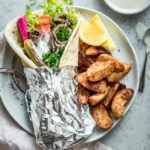 Beef shawarma sandwich rolled up in a thick pita with the bottom half of the wrap covered in aluminum foil sitting on a plate, alongside baked potato wedges and lemon wedges.