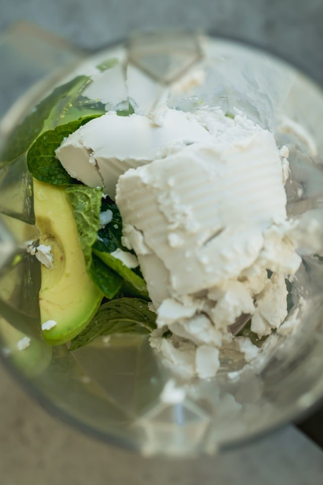 Top view of blender with avocados, coconut milk, mint leaves, maple syrup, lemon juice and bananas underneath - the making of avocado ice cream