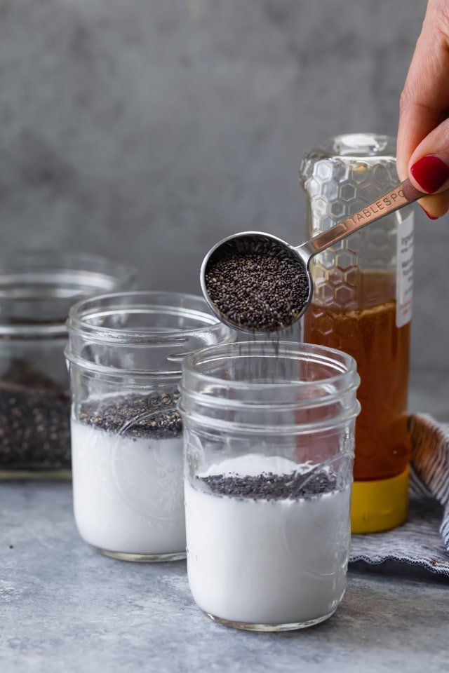 Ingredients to make 3-Ingredient Chia Pudding - almond milk, chia seeds and honey. The chia seeds are being poured into one of the mason jars with a tablespoon.