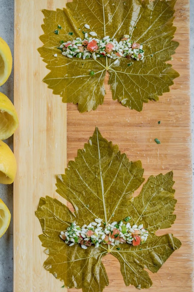 Rolling Vegetarian Stuffed Grape Leaves - two open leaves with a line of the rice mixture laid in the middle of each. Squeezed lemons on the side.