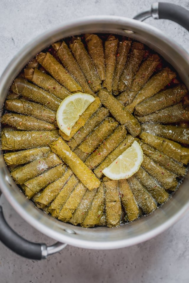 Vegetarian Stuffed Grape Leaves rolled up and stacked in a deep pot with seasoning on top and two slices of lemons - ready to be cooked.