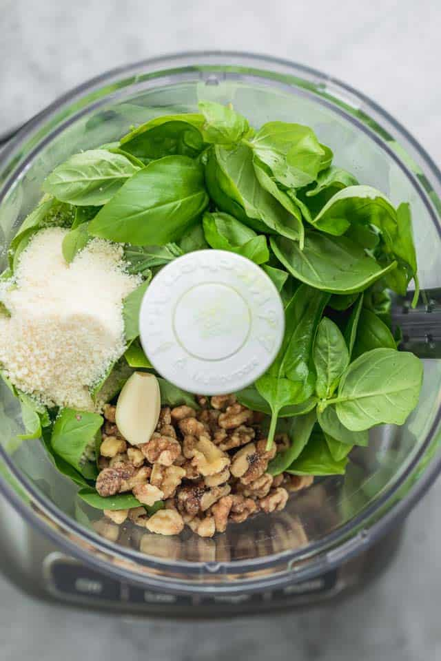 Food processor with ingredients to make pesto - Basil, walnuts, parmesan cheese, garlic, olive oil and lemon juice