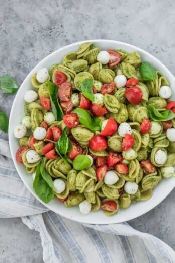 top down shot of Caprese Pasta Salad with Pesto in a large white bowl