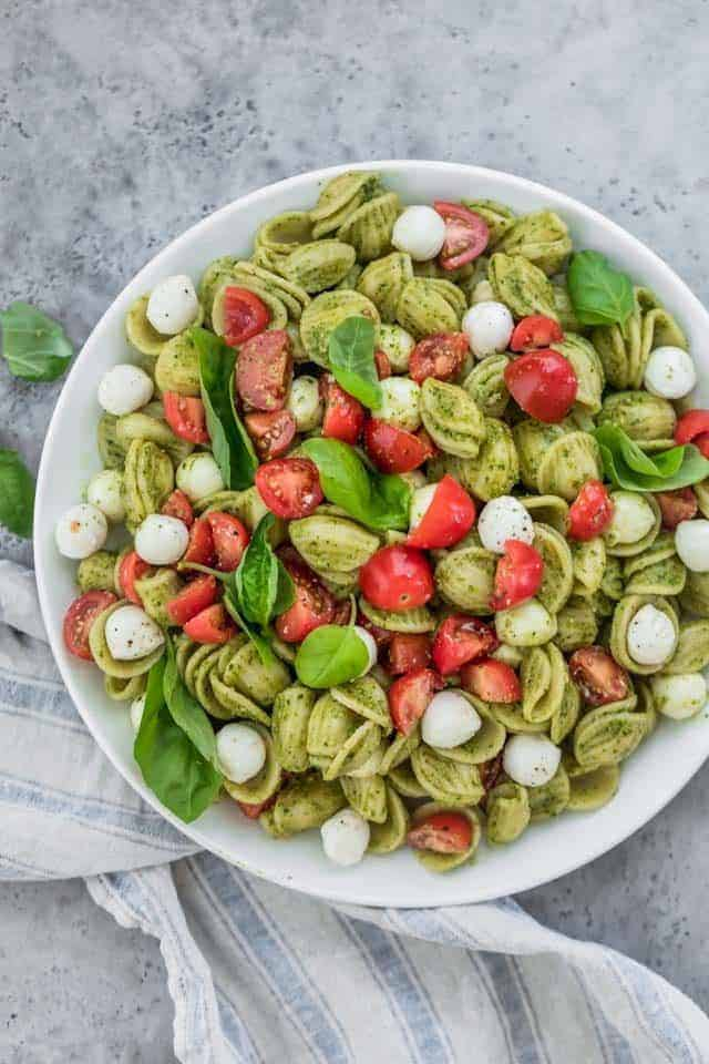 The ultimate summer potluck dish, this caprese pasta salad is made with chunks of pearl mozarella, juicy cherry tomatoes and tossed in a bright pesto sauce!