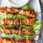 Shish tawook recipe on a platter with garlic sauce