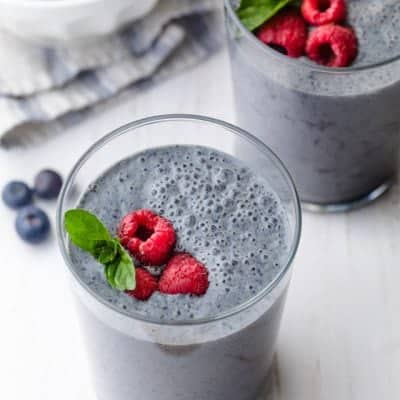 Blueberry banana smoothie topped with raspberries and mint
