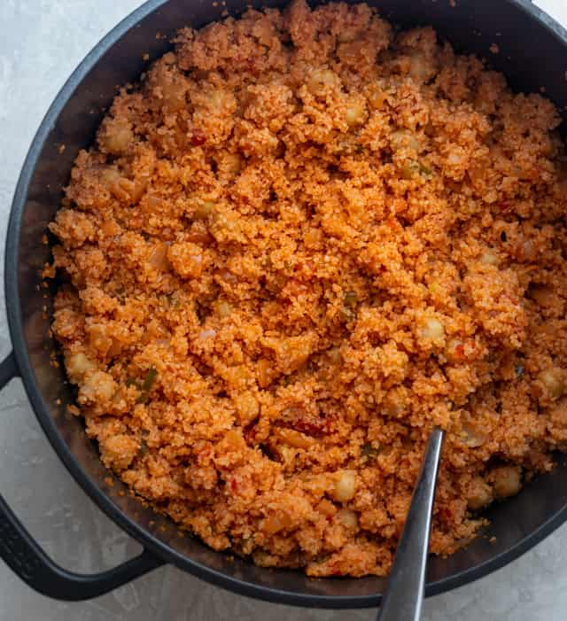 Fluffing the bulgur with a fork after it's done cooking