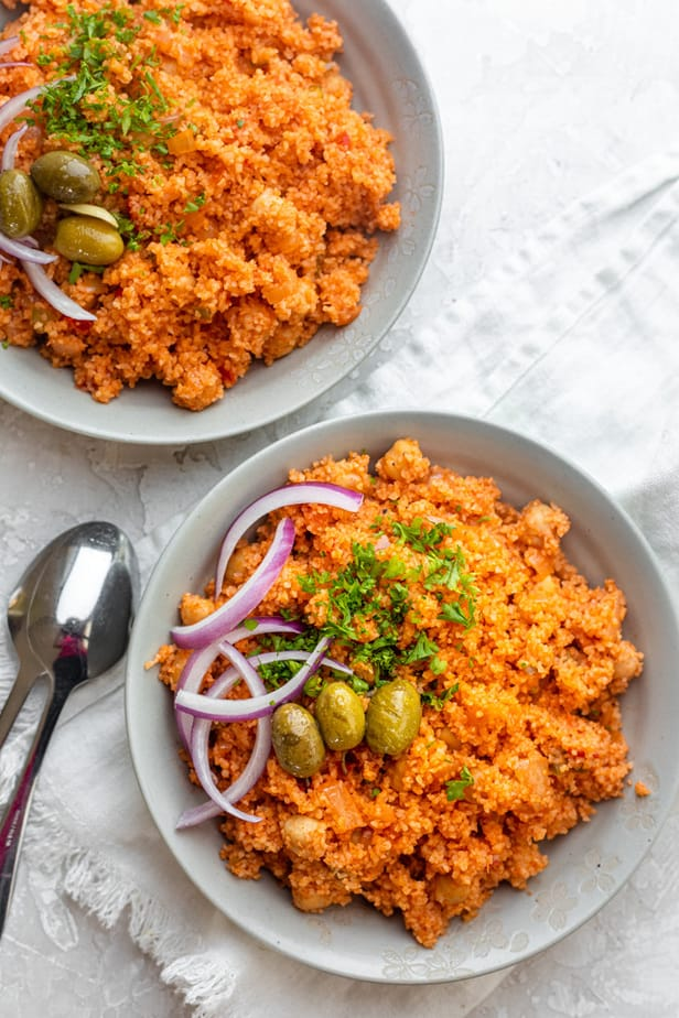 Two plates of bulgur pilaf topped with parsley, olives and onions