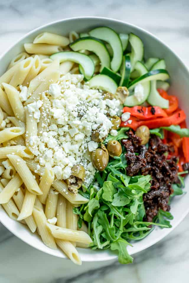 Round white bowl with ingredients for Mediterranean Pasta Salad - including penne pasta, cucumbers, roasted red peppers, olives, sundried tomatoes, arugula and feta cheese