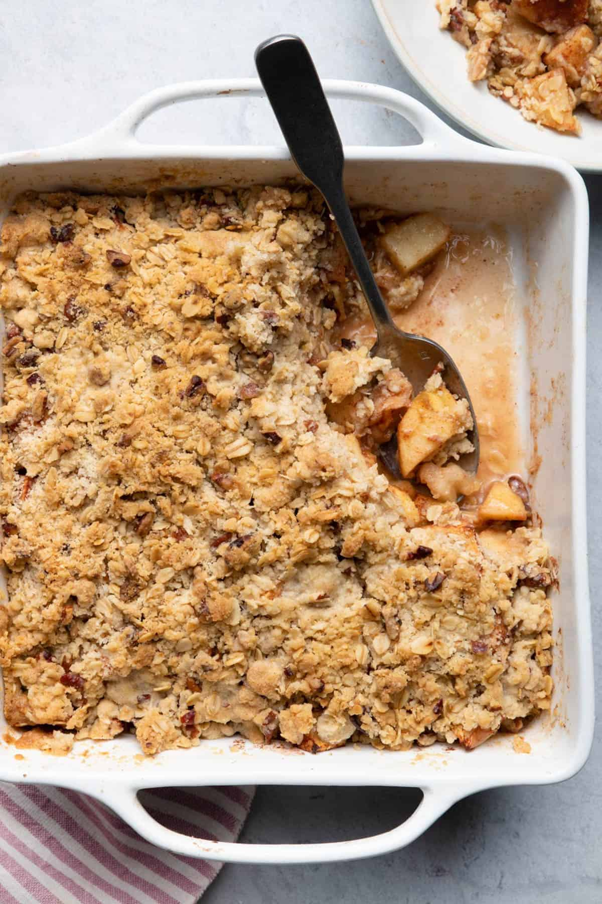 Easy apple crisp out of the oven in a white baking dish with spoon inside