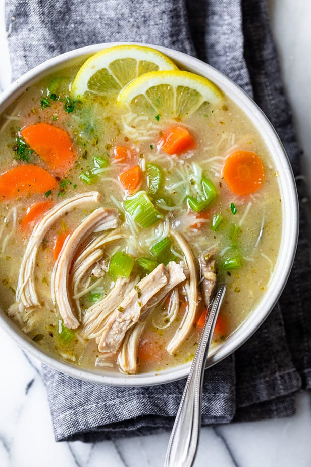 Large bowl of chicken noodle soup with lemon slices