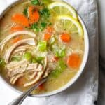 Close up view of the easy chicken noodle soup in a large bowl with lemon slices