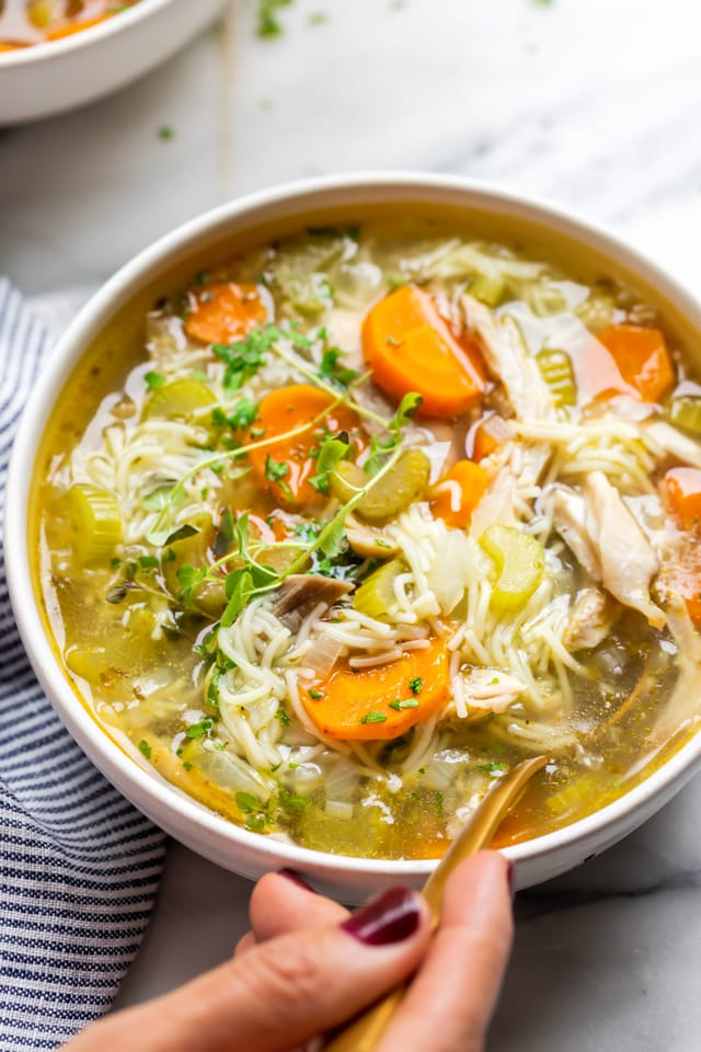 Close up shot of the classic chicken noodle soup with my hands ready to take a bite