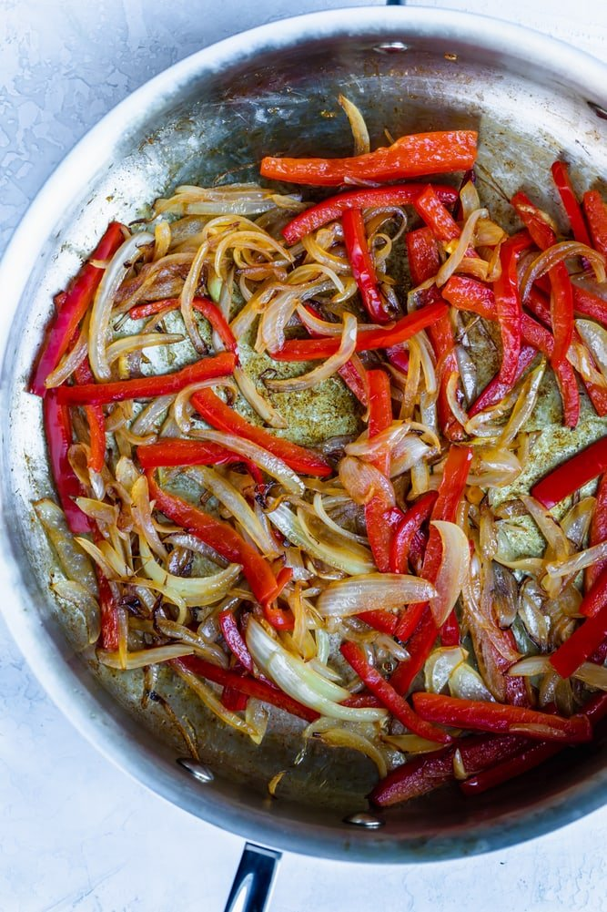 Stainless steel pan with sauteed onions and red peppers