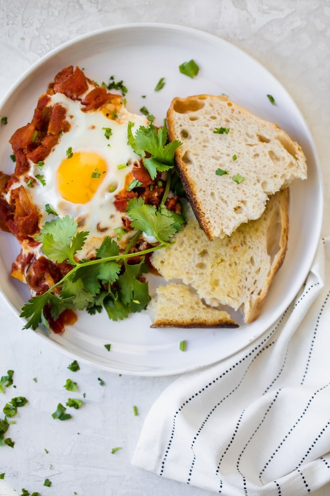 Plate with one serving of Shakshuka with sourdough bread