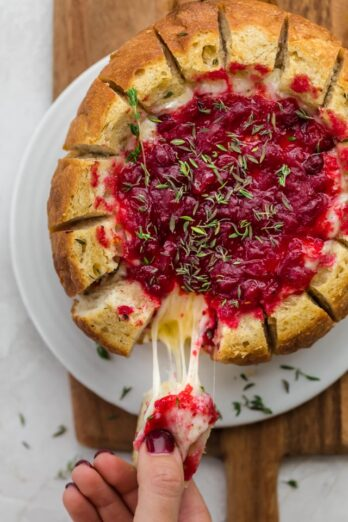 Baked brie cranberry in bread bowl after baked. Slice of bread being pulled away