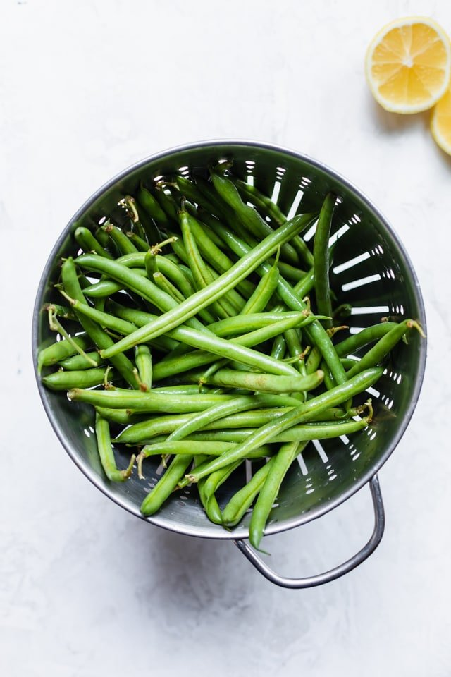 Colander with fresh string green beans after being washed