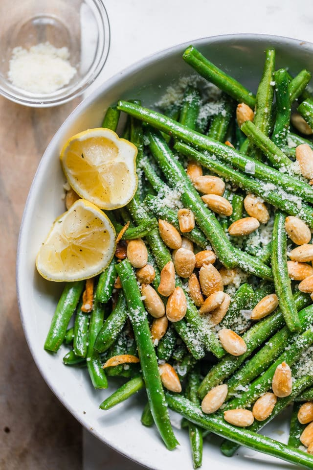 Close up of green beans with almonds with parmesan cheese and lemon wedges