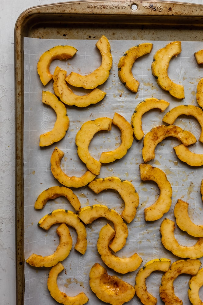 Delicata squash slices arranged on a baking sheet about to get roasted in the oven