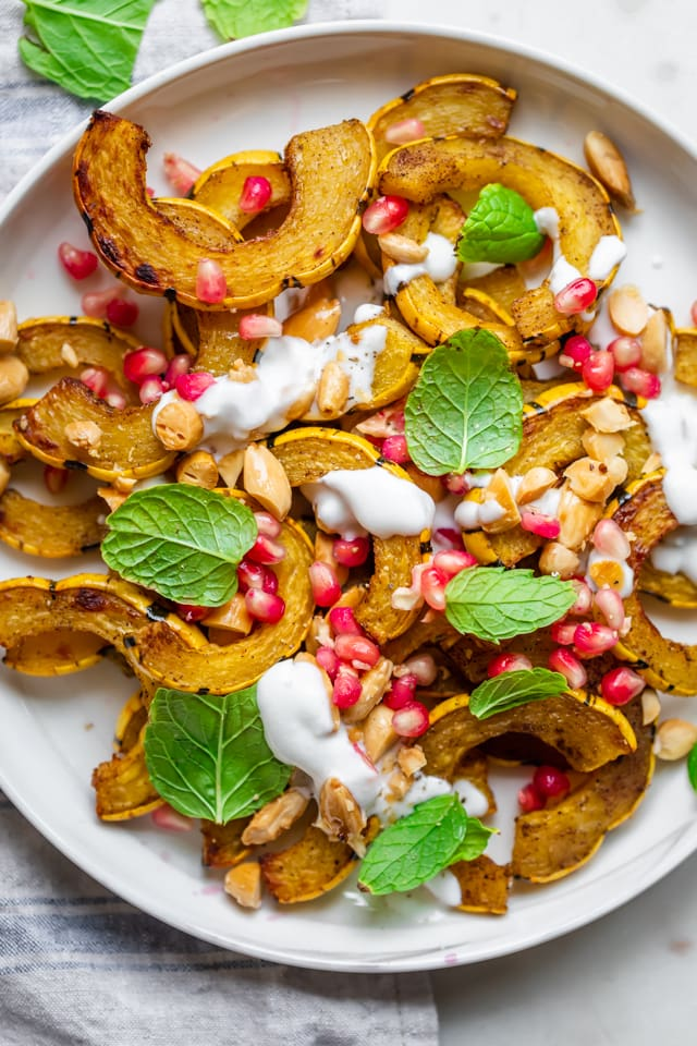 Close up shot of the roasted delicata squash with pomegranate, almonds, mint and yogurt