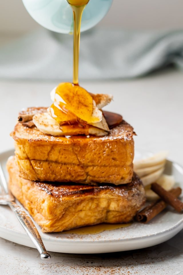 Final plating of the stuffed french toast with two stacked on top of each other, topped with bananas and maple syrup getting drizzled on top