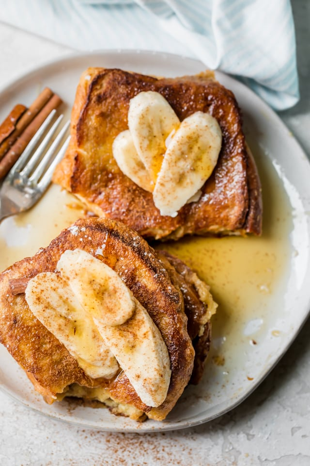 Top view of two servings of stuffed french toast sitting on a plate with maple syrup and sliced bananas
