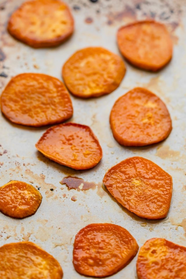 Sliced sweet potatoes on a baking sheet after being baked