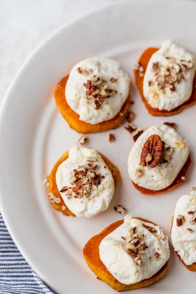 Sweet potato rounds on a white dish with melted marshmallows and pecans