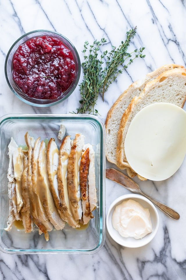 Marble background with sourdough slice bread, cheese, turkey, cranberry sauce, thyme, and mayonnaise