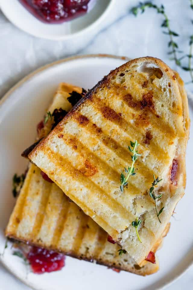 Final outcome of the turkey panini showing two halves of the sandwich stacked on top of each other with a aside of cranberry sauce