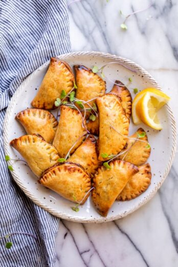 Final plated dish of the broccoli and cheese hand pies on a white plate with garnish and lemon slices