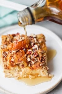 Close up shot of slice of easy french toast casserole with maple syrup getting poured on top