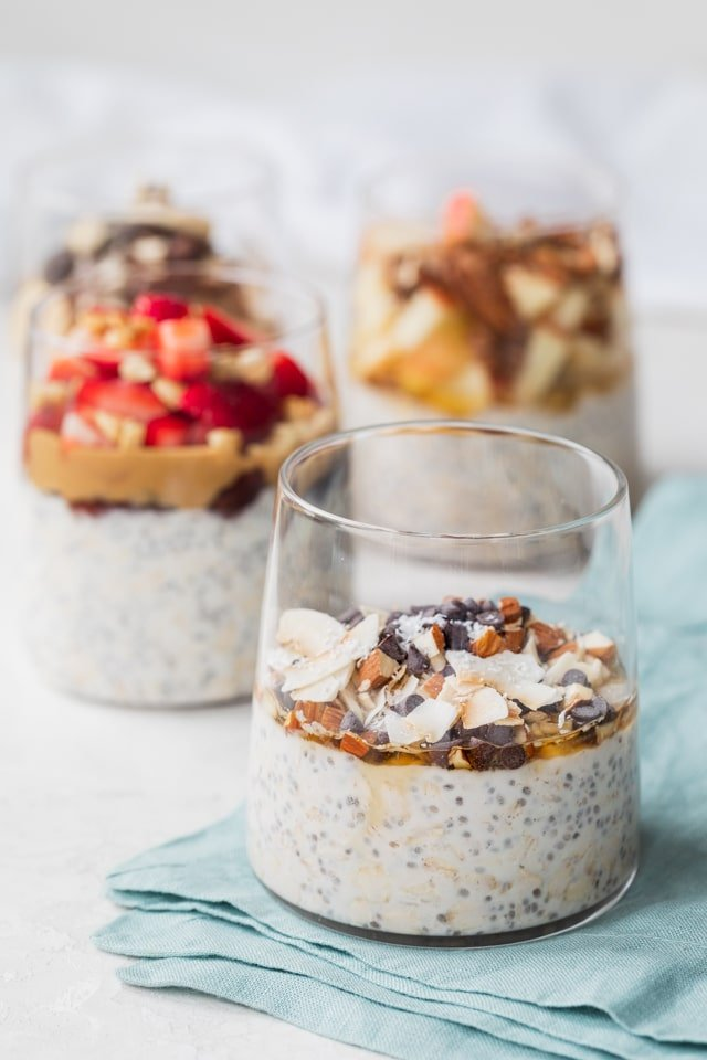 Almond joy overnight oats in a glass cup with other overnight oats in background