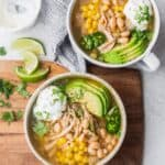 Final easy white chicken chili served in two bowls with toppings