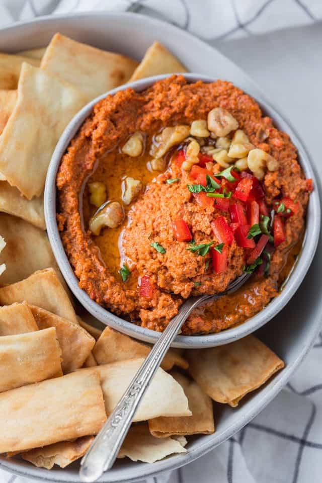 Close up shot of muhammara with a spoon inside the dip