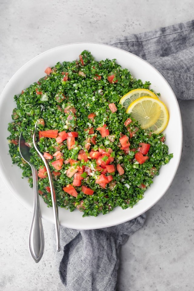 Final plated bowl of tabbouleh salad garnished with lemon slices