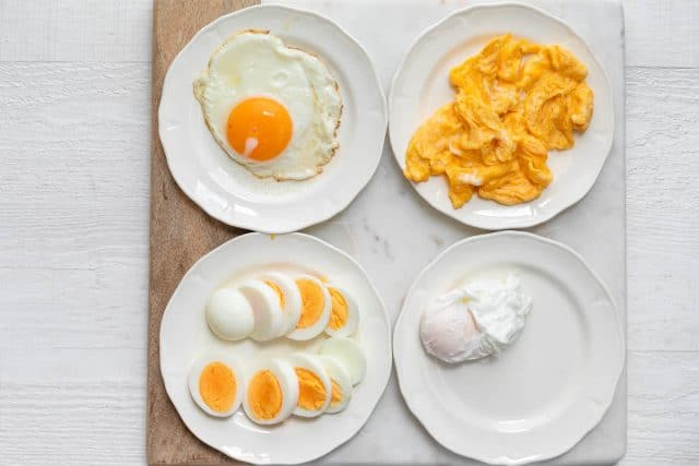 4 plates with 4 types of eggs for topping the toast