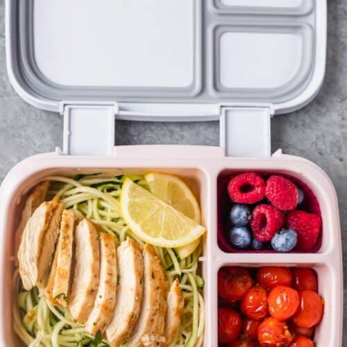 Lemon Garlic Chicken meal prep with zoodles, tomatoes and fruit