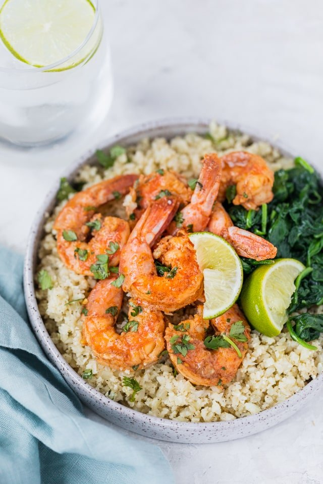 Plate of cilantro lime cauliflower rice with shrimp and spinach