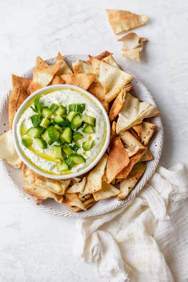 Large platter of toasted pita chips with feta dip