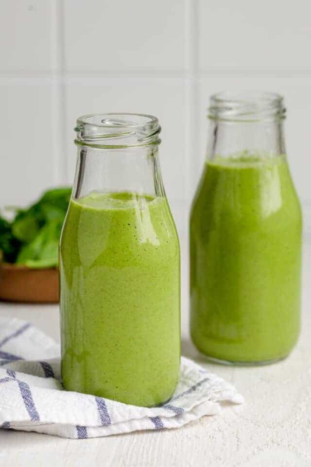 Two small milk jugs of green smoothies with bowl of spinach in background