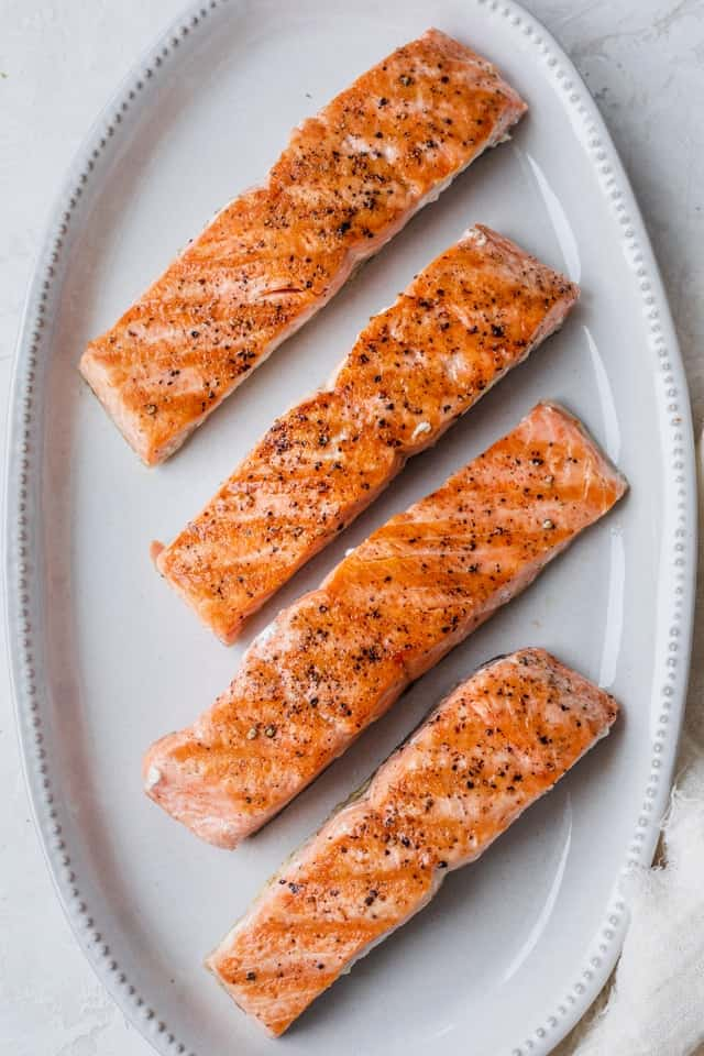 Grilled salmon on a white dish before topping with the citrus salsa