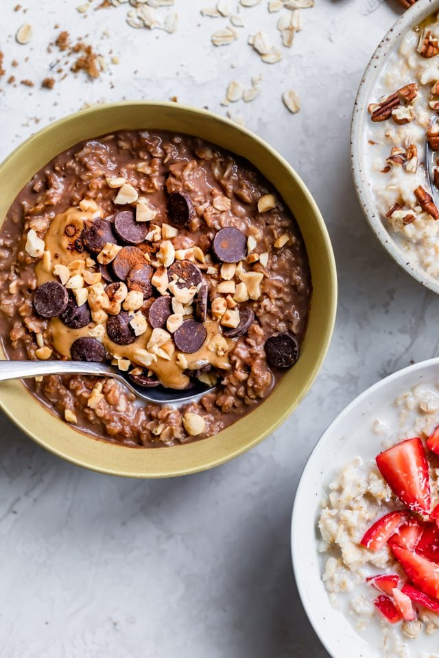 Three bowls of oatmeal with focus on the chocolate peanut butter oameal