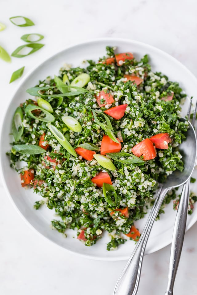 Close up shot of the quinoa tabbouleh on a plate with a spoon and fork