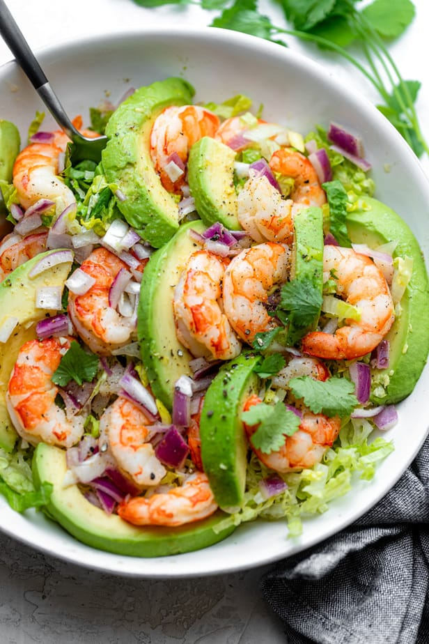 Serving shrimp avocado salad with a large spoon and fork