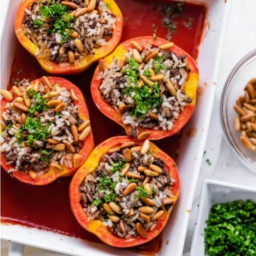 Baking dish with stuffed peppers, topped with pine nuts adn parsley