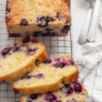 Lemon blueberry bread on a wire rack with forks on the side
