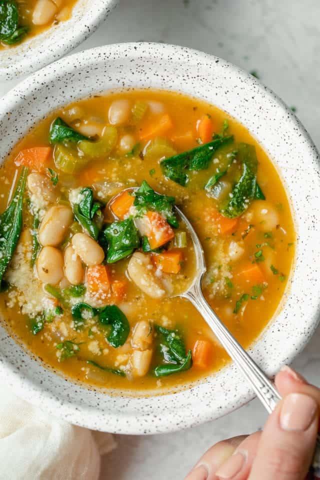 Mediterranean white bean soup in a large white bowl